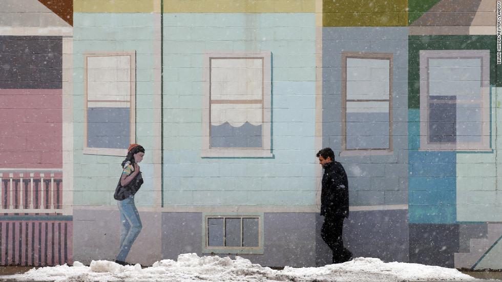 A pedestrian walks past a mural at the beginning of a winter storm in Somerville, Massachusetts, on Thursday, March 7.