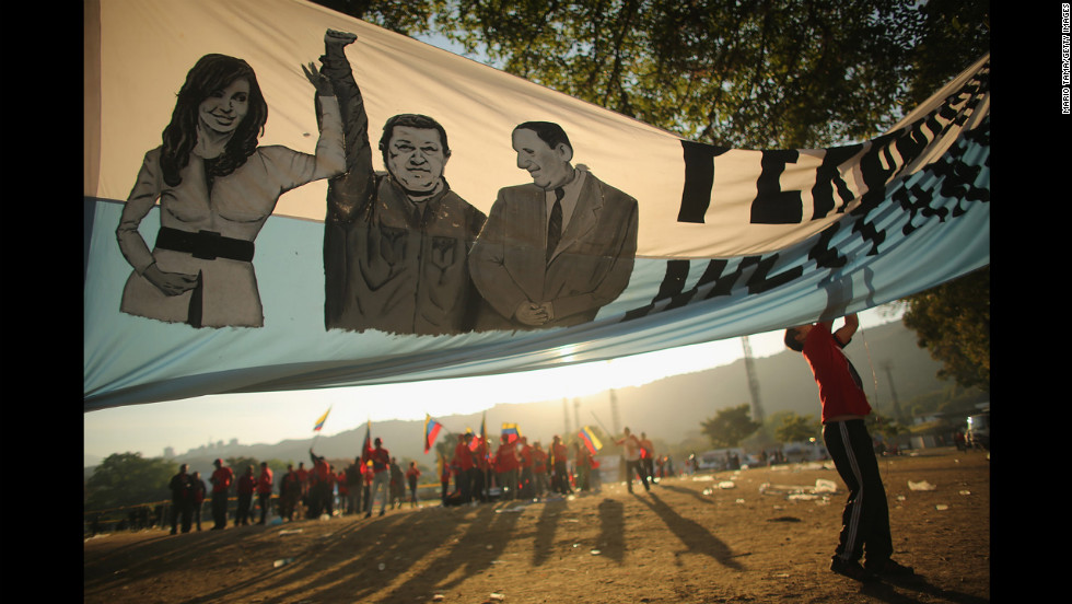 A man adjusts a banner before the start of Chavez's funeral outside the Military Academy.