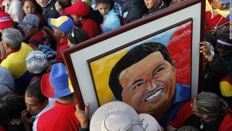 Supporters of Chavez hold a portrait of him as they wait for a chance to view his body at the military academy in Caracas on March 8.