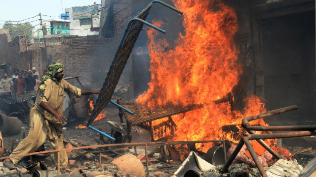 An angry Pakistani demonstrator torches Christian's belongings in Lahore during a protest over a blasphemy row.