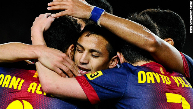 Alexis Sanchez is swamped by his teammates after scoring the opening goal against Deportivo La Coruna on Saturday.