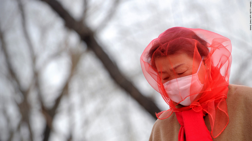 A Chinese woman covers her head with a scarf as she walks near Tiananmen Square in Beijing on Saturday, March 9, as strong winds and dust storms swept the Chinese capital.