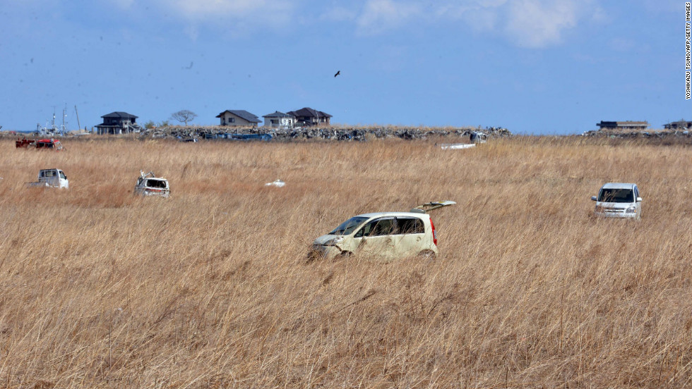 Vehicles that were abandoned two years ago sit in a field of reeds in Namie on Monday.