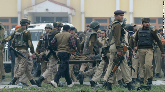 Indian paramilitary personnel carry away a fallen comrade in Srinagar on Wednesday. Five Indian officers died at the police camp.