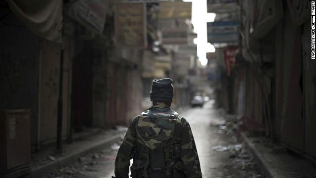 Rebel fighter walks through the ravaged Sit al-Ruba shopping street in the city of Deir Ezzor, Syria, on February 16, 2013.