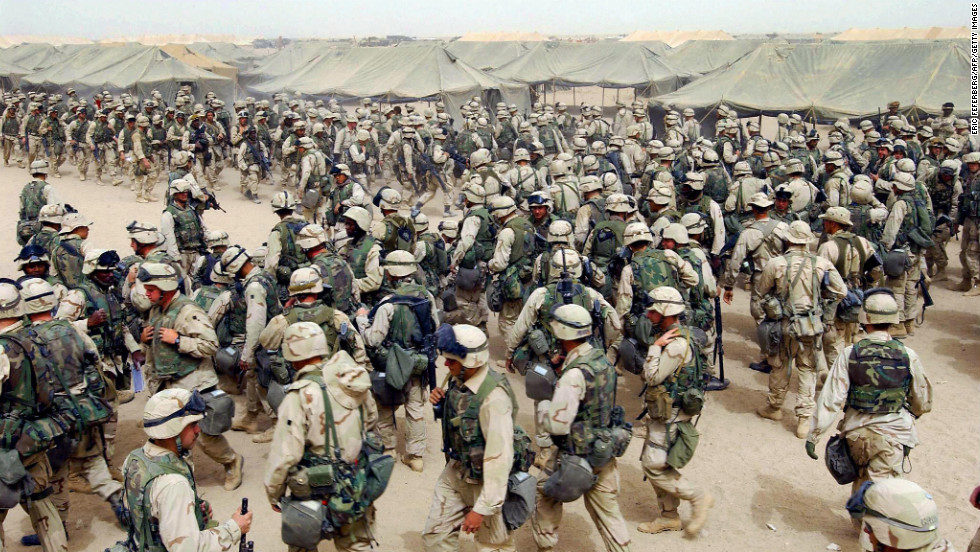 "U.S. Marines in northern Kuwait gear up after receiving orders to cross the Iraqi border on March 20, 2003. It has been 10 years since the American-led invasion of Iraq that toppled the regime of Saddam Hussein. Look back at moments from the war and the legacy it left behind. For more, view <a href=""http://www.cnn.com/SPECIALS/world/iraq/index.html"" target=""_blank"">CNN's complete coverage of the Iraq War anniversary.</a>"