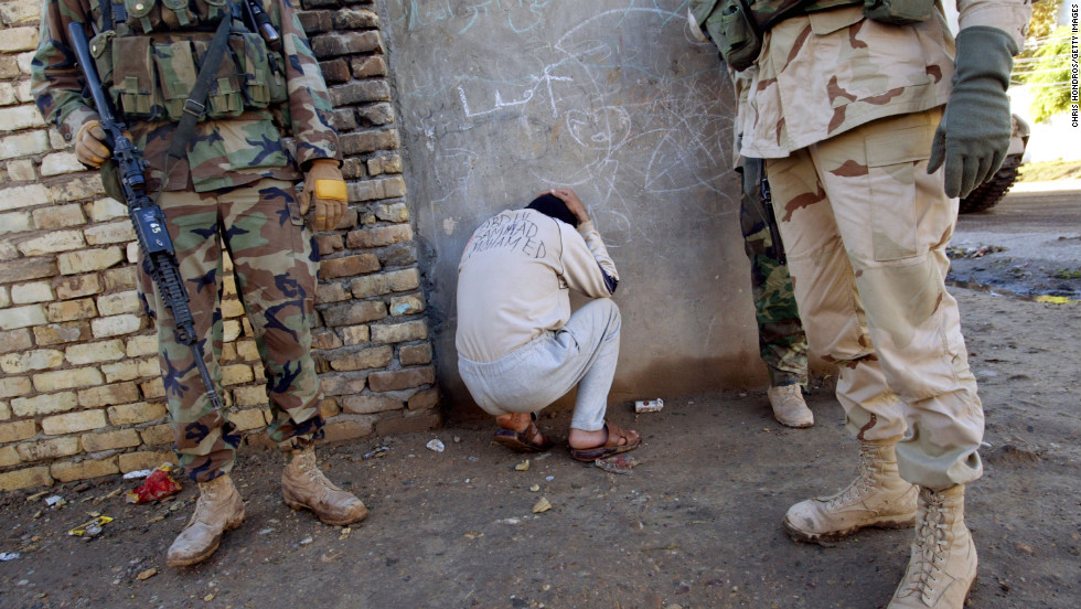 A bound Iraqi informer, with his name inked in English across his back, crouches beside soldiers in the 4th Infantry Division after providing outdated information during a morning raid in in Samarra on December 19, 2003.