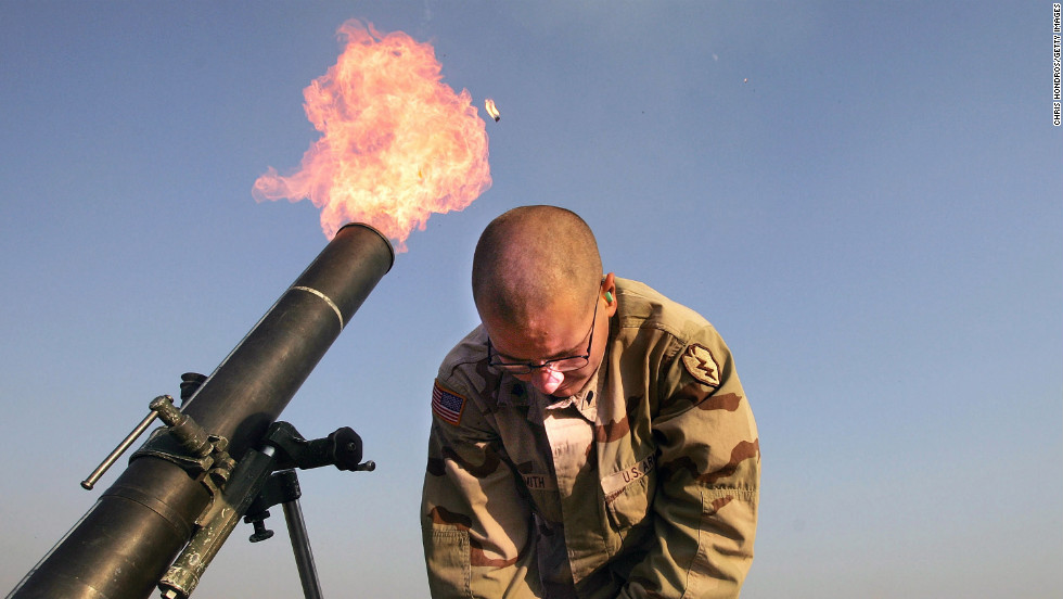 "Spc. Franklin Smith pulls away as a mortar blast is fired from the edge of the U.S. airbase in Tal Afar on January 17, 2005. U.S. teams would frequently fire ""harassment and interdiction"" mortar fusillades toward suspected enemy positions."