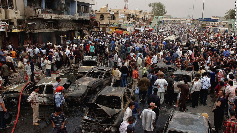 People gather at the scene of a car bombing near a busy market in eastern Baghdad on May, 12, 2005.