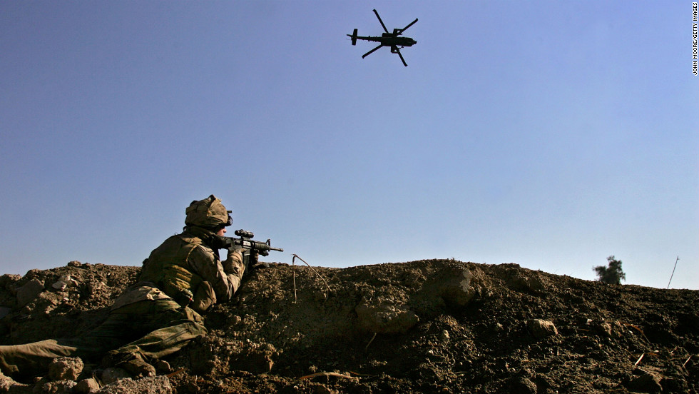 An American Apache helicopter provides air support while a Marine takes aim after being fired upon by insurgents near the Euphrates River in Ramadi on February 2, 2007.