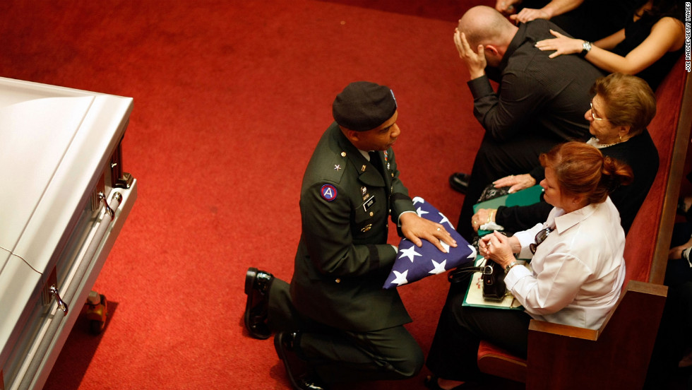 Army Brig. Gen. Nolen V. Bivens presents an American flag to Maribel Ferrero during the funeral of her 23-year-old son, Army Pfc. Marius L. Ferrero, in Miami. He was killed by a roadside bomb while serving in Iraq.