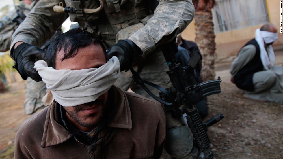 A U.S. soldier blindfolds an Iraqi man during a raid in Mukhisa on December 3, 2007.  Seven men were detained after multiple assault rifles were found in the house.