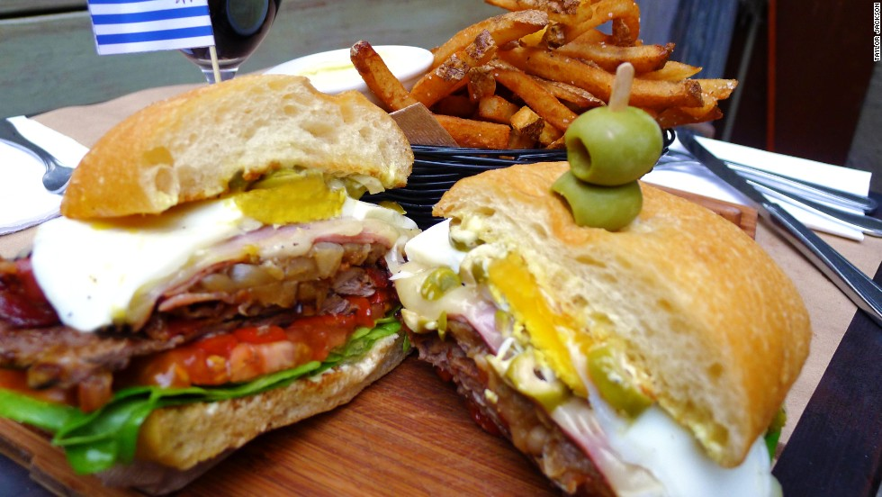 The Uruguayan chivito piles skirt steak or filet mignon with layers of ham and bacon, accompanied by onion, mayonnaise, lettuce, tomato, mozzarella, olives, hard-boiled egg and lettuce. Pictured: chivito from Tabaré in Brooklyn.