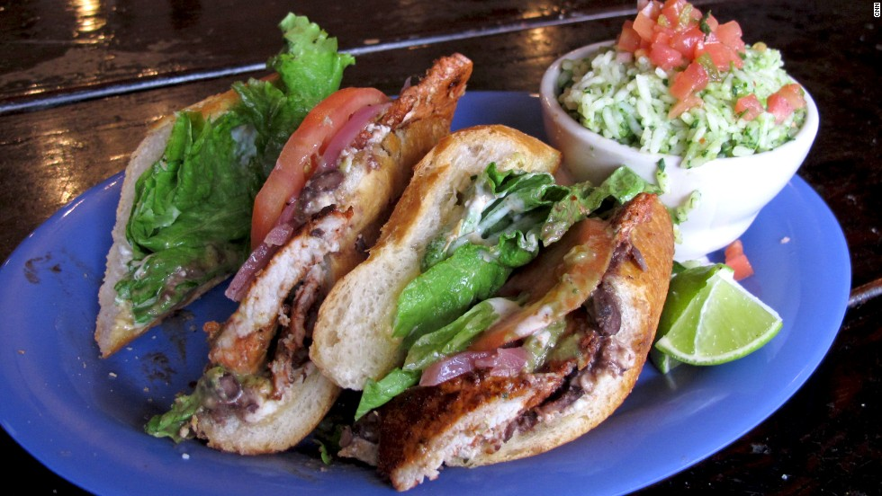 The Mexican torta is typically served on a crusty, football-shaped roll. Popular tortas include fillings such as carne asada or chorizo accompanied by tomato, onions, jalapeño and avocado. Pictured: Achiote-citrus pork torta from Torta-Landia! in Portland, Oregon.