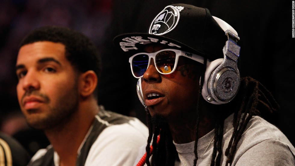 Lil Wayne and hip-hop artist Drake, left, sit courtside during the 2012 NBA All-Star Game.