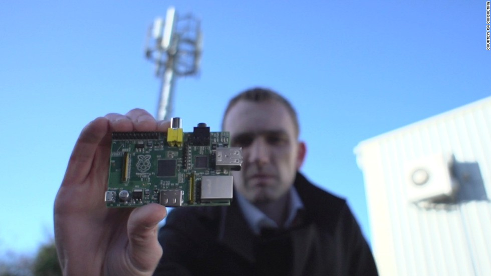 Alastair Smith, a wireless technology expert at PA Consulting Group, holds up a Raspberry Pi in front of a cell phone tower. The team created a private mobile-phone network by connecting the RPi, a $25 singleboard computer, to a radio interface.