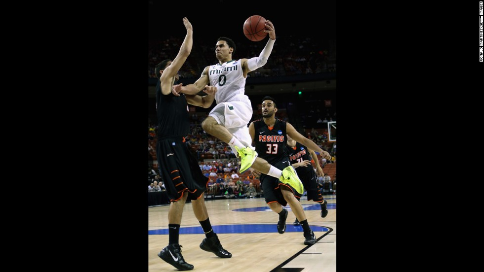 Shane Larkin of the Miami Hurricanes, center, drives on Rodrigo De Souza of the Pacific Tigers on March 22.