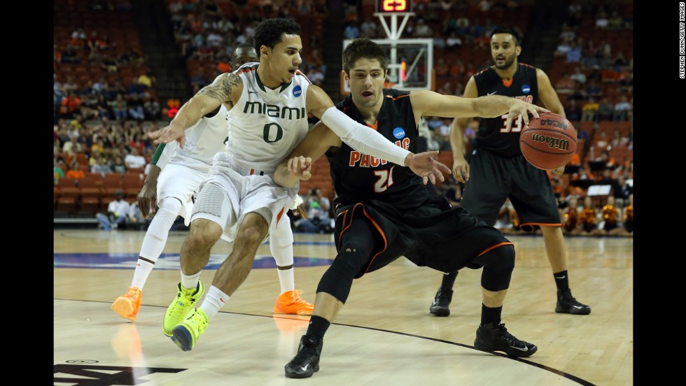 Rodrigo De Souza of the Pacific Tigers, center, moves the ball against Shane Larkin of the Miami Hurricanes on March 22.