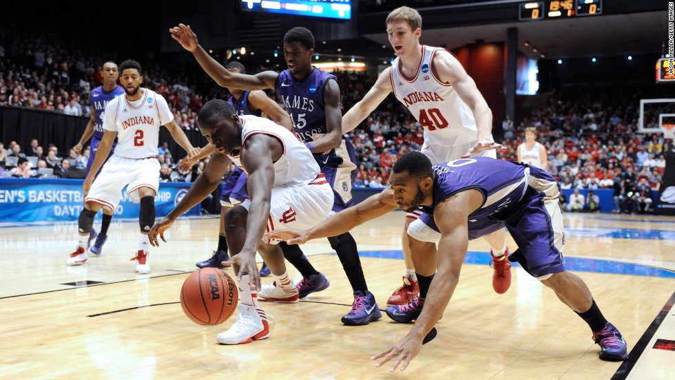 Victor Oladipo of the Indiana Hoosiers, second from left, and A.J. Davis, right, of the James Madison Dukes go for a loose ball on March 22 in Dayton, Ohio.