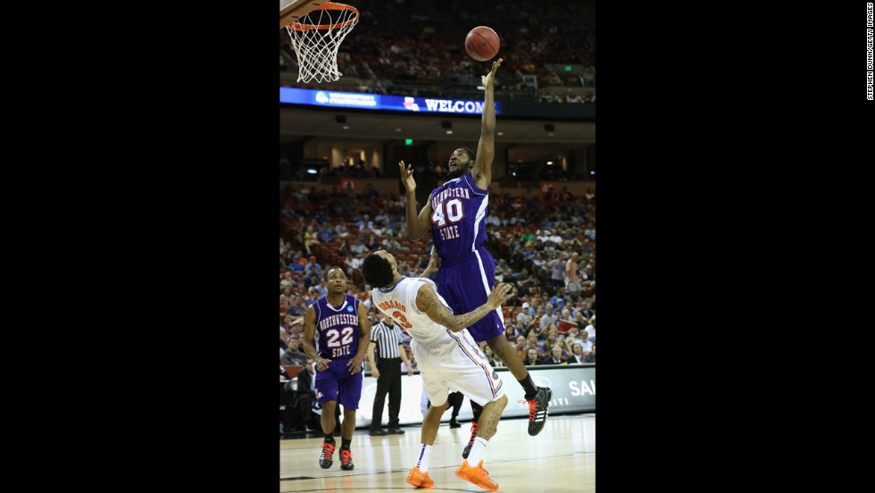 Marvin Frazier of the Northwestern State Demons, center, goes up to the basket over Mike Rosario of the Florida Gators on March 22.
