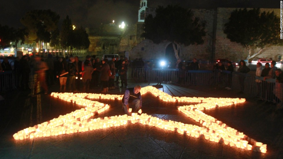 Members of Palestine Wildlife Society outline the star of Bethlehem with candles at the Manager Square in front of the Church of the Nativity in the West Bank town of Bethlehem on March 23 to mark the Earth Hour for the first time in Palestine.