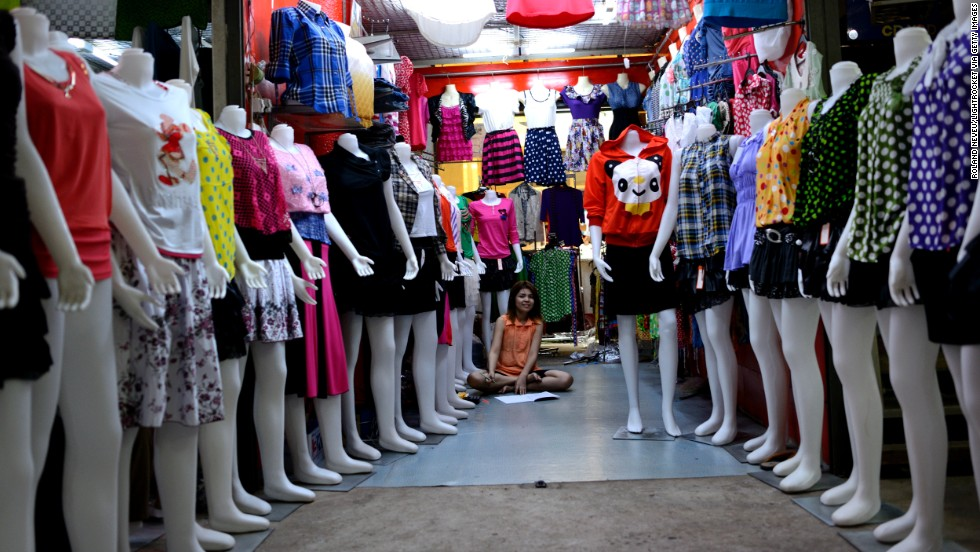 A woman sits in her shop lined with mannequins in a shopping center in Mawlamyine.