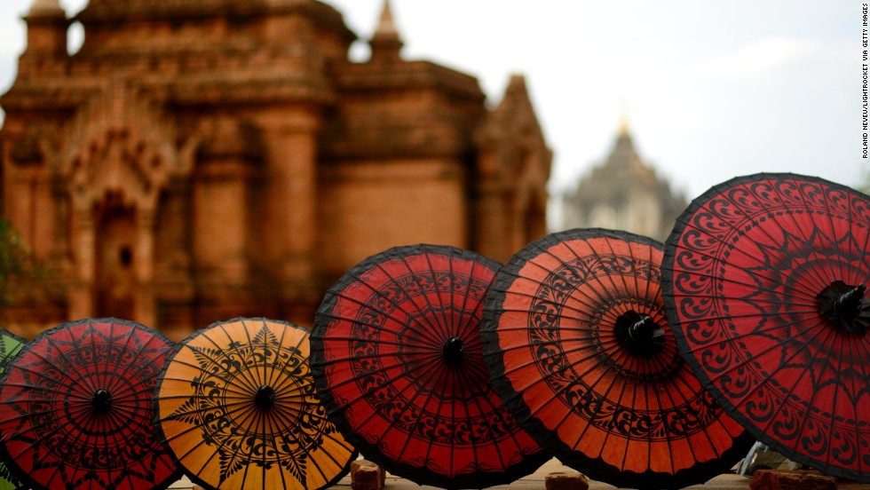 A line of umbrellas sits in front of an old building in Bagan.