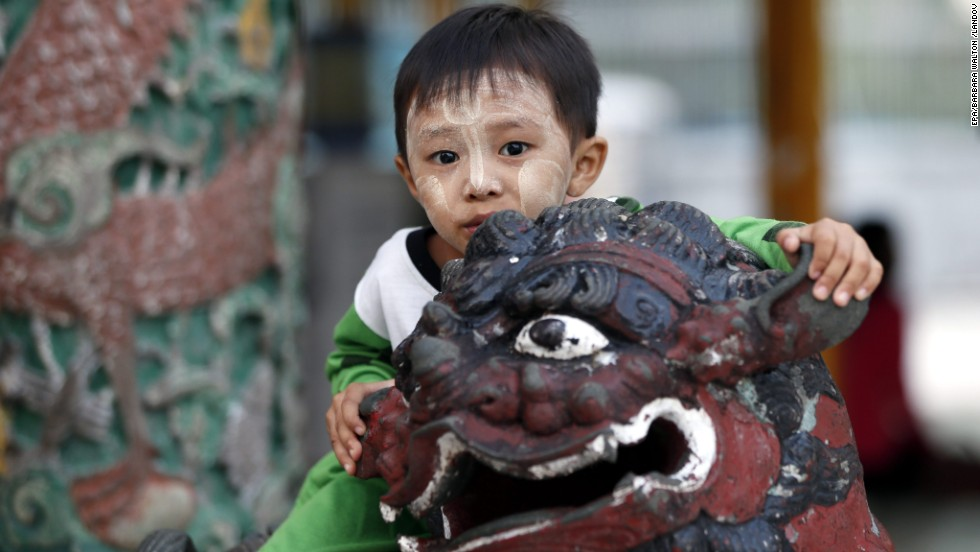 A Burmese boy climbs on a gargoyle statue at the sacred Shwedagon Pagoda in Yangon.