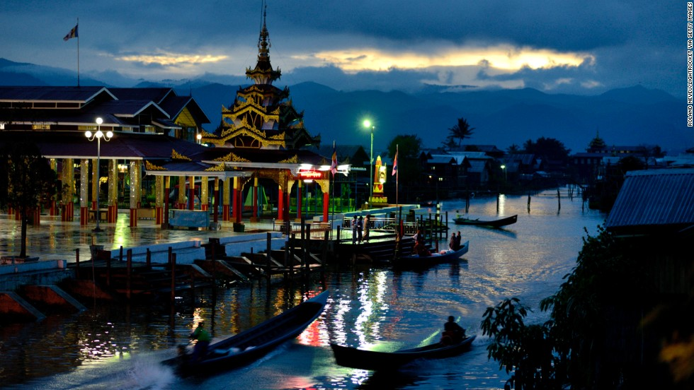 The temple of Phaung Daw U, the largest on Inle Lake, is lit as dusk falls in the village of Ywama.