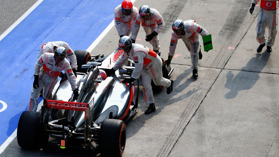 Jenson Button's car is pushed back to the pit area after his crew let the McLaren leave with a loose front wheel. It ruined the 2009 world champion's chances of earning points and he retired before the end of the race. However, his new Mexican teammate Sergio Perez finished ninth.