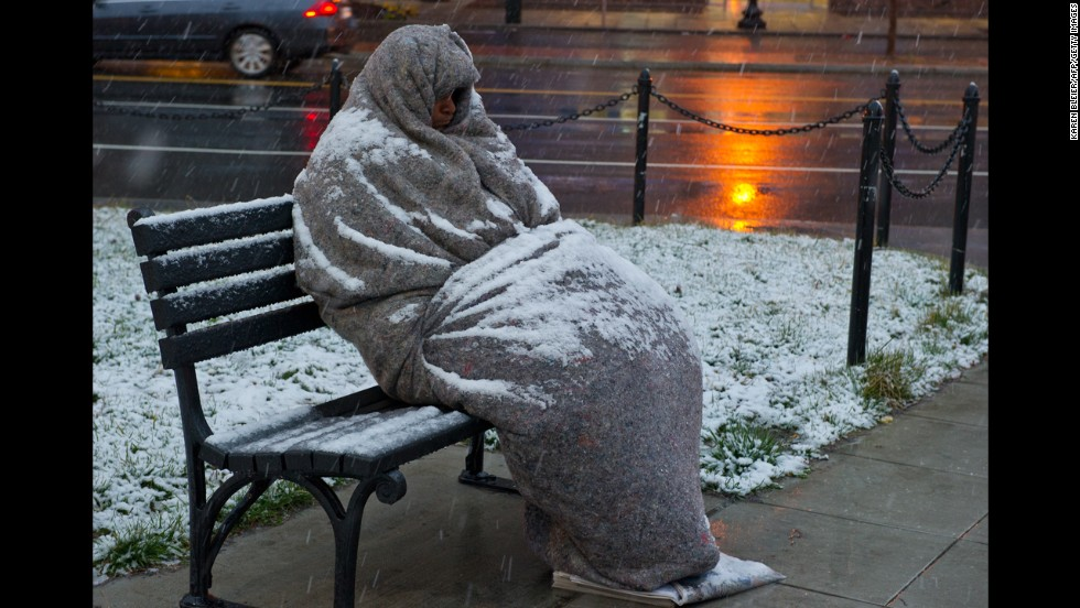 Snow collects on a man sleeping on a bench early Monday, March 25, in Washington, D.C.