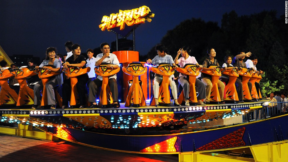 A group enjoys a ride on one of the many attractions at a funfair in Pyongyang. The city hosts new funfairs and amusement parks every night. North Koreans who can't afford the rides come just to watch.