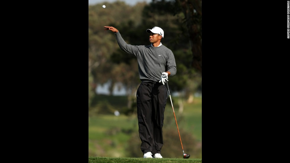 Woods tosses his ball to his caddy at the Farmers Insurance Open at Torrey Pines in January 2013, when he won his 75th PGA Tour title.