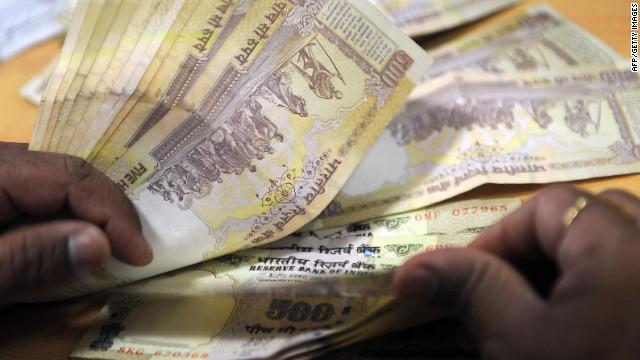 A bank cashier counts Indian Rupee notes at a bank in Mumbai on November 22, 2011.