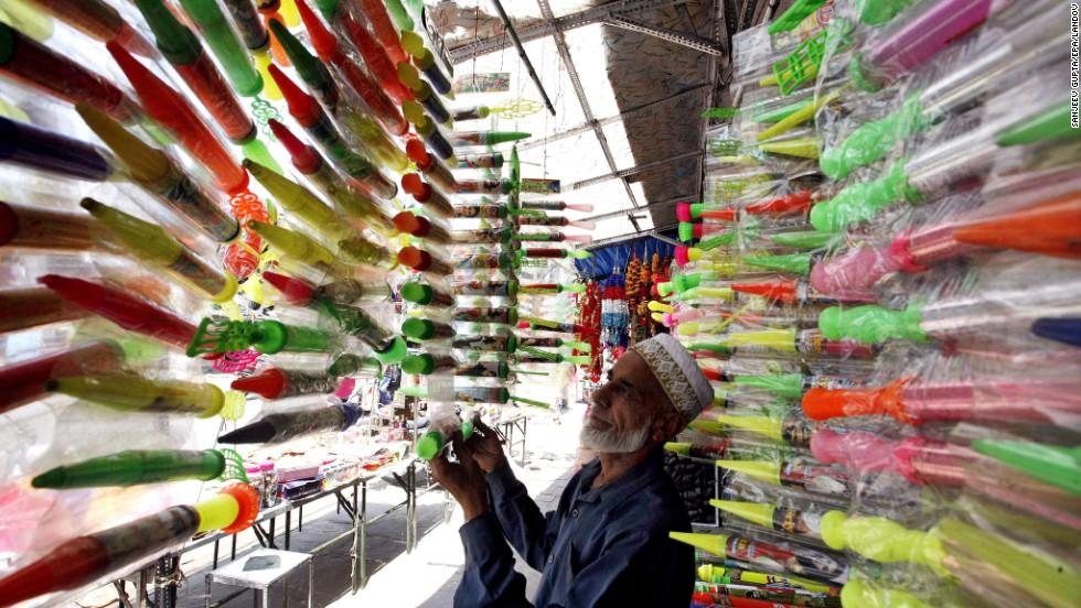 A shopkeeper sets up water canon for sale in a market ahead of the festival in Bhopal, India, on Monday, March 25.