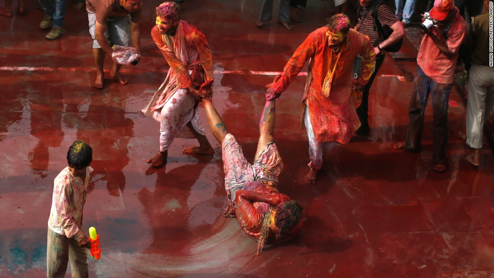 Men drag a boy on the ground to cover him in reddened water in Nandgaon, India, on Friday, March 22. Lathmar Holi takes place before Holi, officially, in the Nandgaon and Barsana villages and is deeply rooted in Hindu tradition, but Lathmar Holi revelry has taken place all over during the past week.