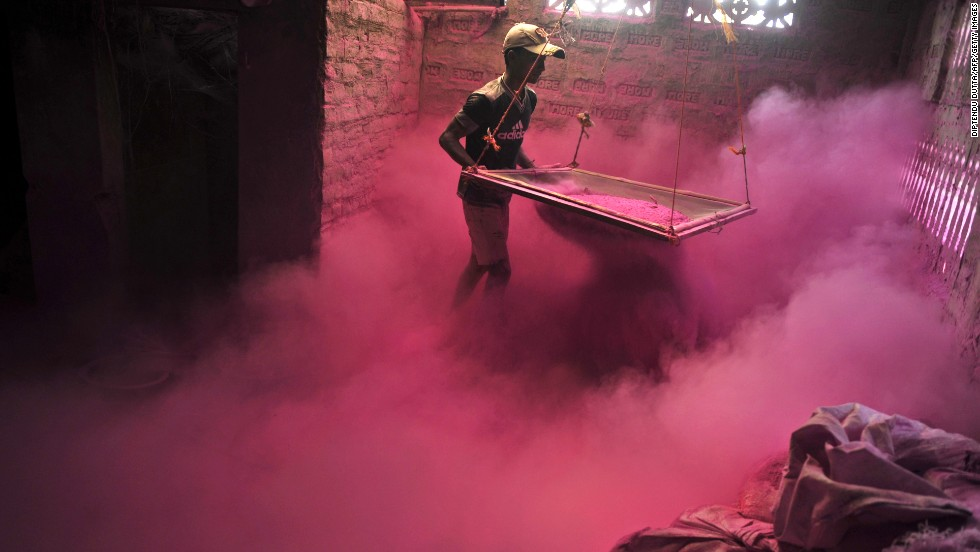 A man sifts colored powder to be used during celebrations on the outskirts of Siliguri, India, on Wednesday, March 20.