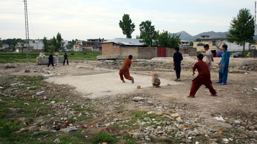Children play cricket near the site of the demolished compound.
