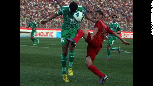 A Syrian player, wearing red, vies for the ball against an Iraqi player during Tuesday's friendly match in Baghdad.