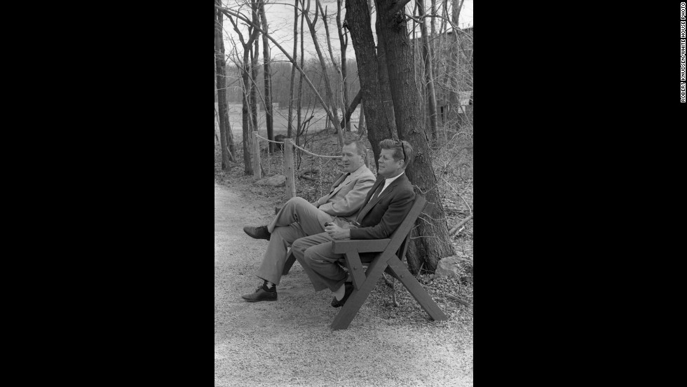Kennedy holds a pipe while he and Fay sit on a bench.