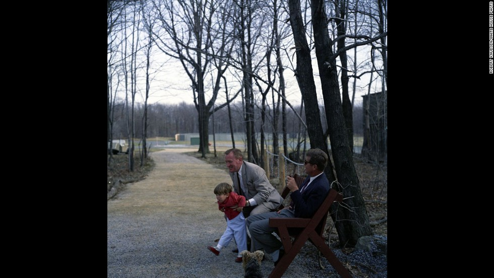 "Kennedy looks on as Under Secretary of the Navy Paul ""Red"" Fay picks up the president's son."