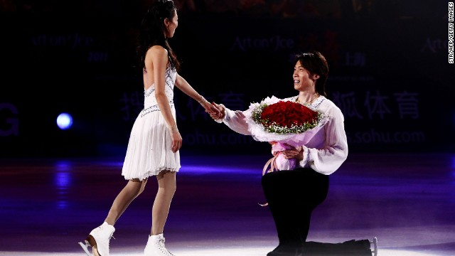 China's Olympic silver medal figure skater Tong Jian, right, proposes to his girlfriend and skating partner Pang Qing at the end of a skating exhibition in Shanghai in 2011.