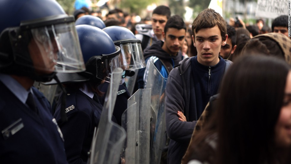 Riot police stand guard outside the European Union House as college students gather for a protest in Nicosia, Cyprus, against a bailout  on March 26.