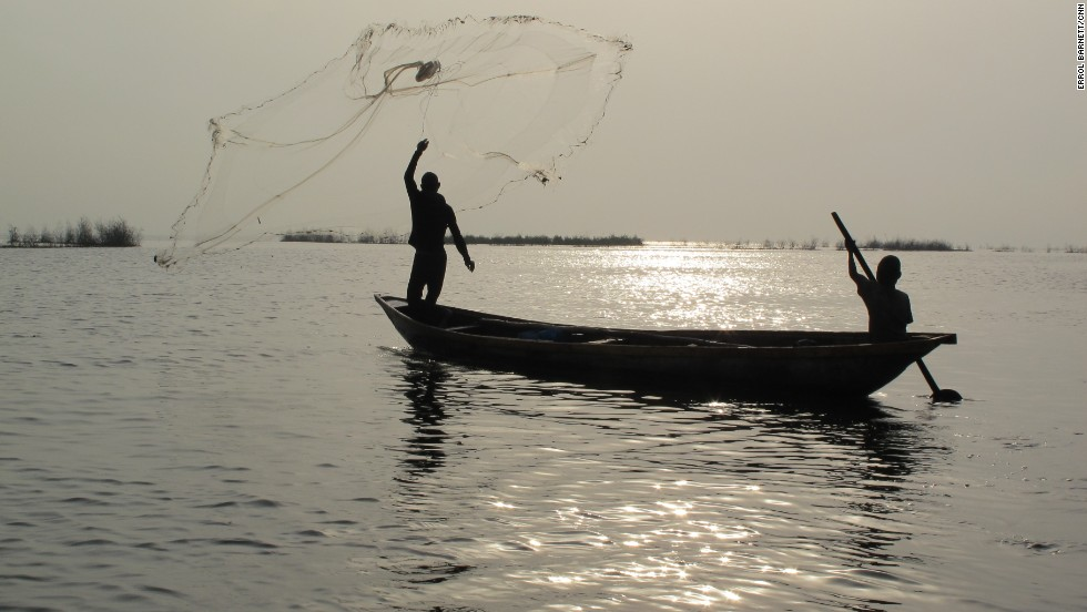A fisherman throws out his net on the lagoon's calm waters. Fisherman immigrating from Benin and Togo initially settled Makoko over a century ago. But as the population of Lagos exploded to its current size of at least 15 million, so too did the population of Makoko. Estimates are that anywhere from 85,000 to 250,000 people live there.