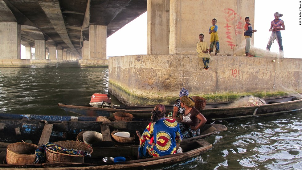 "Women and children congregate under the Third Mainland Bridge, which connects Lagos Island with Nigeria's mainland. Barnett describes the image as representing two separate worlds, ""Many who travel over this bridge daily tell me they've never been to Makoko and don't know what life is like for people living there."""