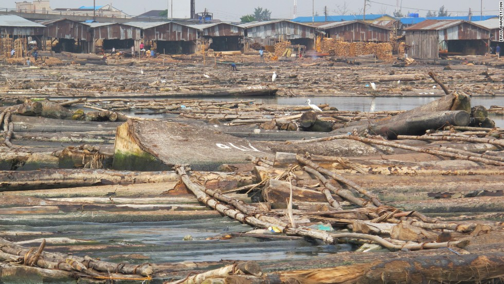 Tree trunks clog the lagoon's waters at the foot of a series of sawmills in the distance. This wood is floated into the lagoon surrounding Lagos via nearby rivers where workers will slice it into planks. Major floods can bring chaos to this system, as well as to the lives of residents.