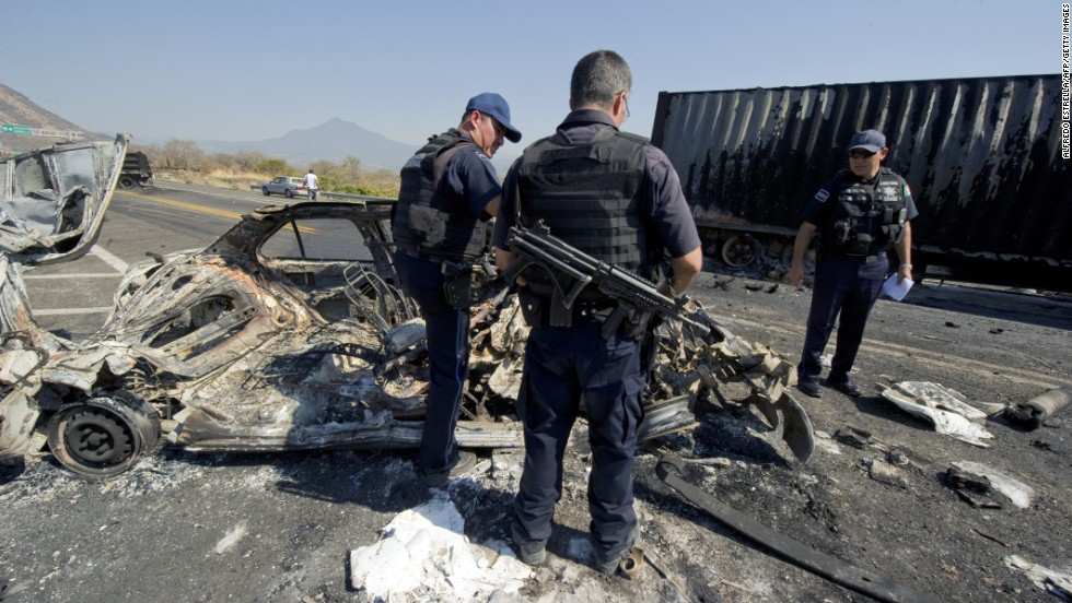 Mexican federal police officers inspect the charred wreckage of a car used to make a barricade blocking the Apatzingan-Uruapan road in Michoacan on December 11, 2010. Gunmen from the La Familia drug cartel blocked several roads in the state during a confrontation with the federal police, according to the state government.