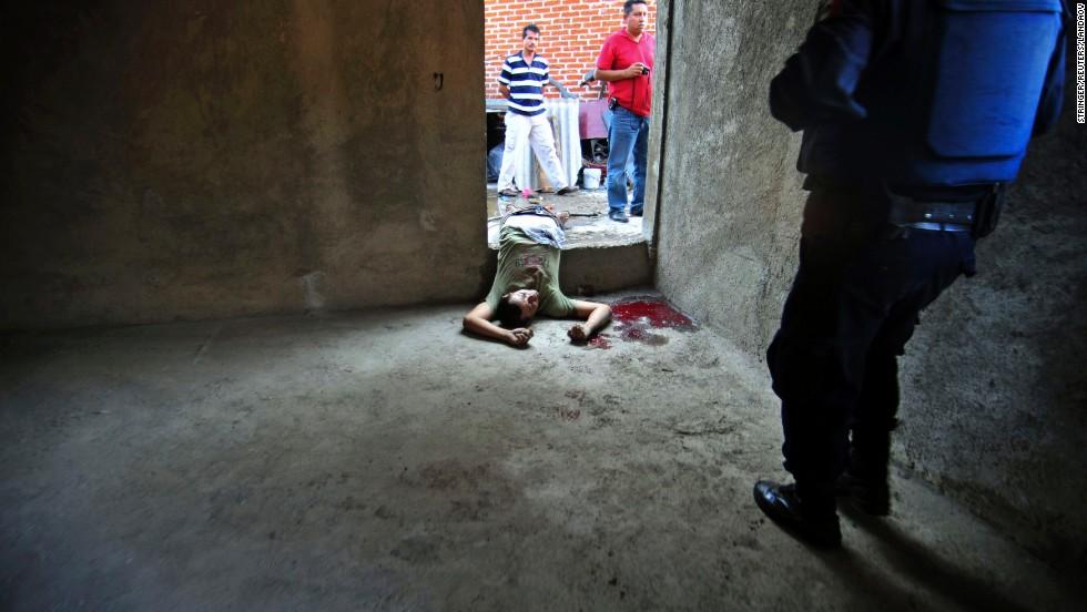 Police walk near a victim of a shootout between the drug cartels La Familia and Los Zetas in Uruapan  on December 14, 2009.