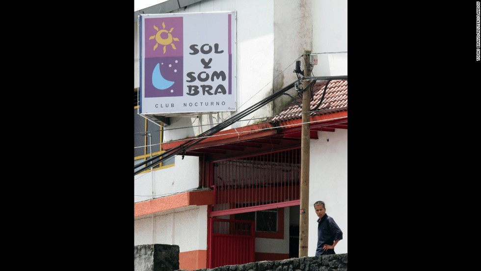 "A man stands in front of the ""Sun and Shadow"" nightclub, where gunmen in ski masks rolled five severed heads onto the dance floor, on the edge of the city of Uruapan on September 7, 2006."