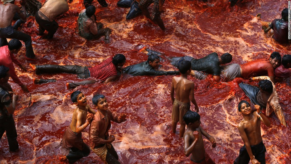 Men are dragged on the ground to cover them in red water during huranga on March 28.